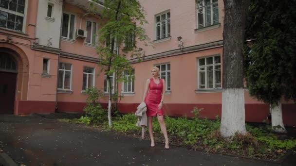 Fotomodell im roten Kleid spaziert über den alten Hof.