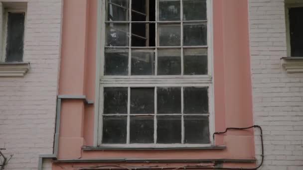 Stará budova s velkými okny na starém dvorku.