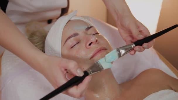professionelle Kosmetikerin, die Maske mit Pinseln auf das Gesicht der Frau aufträgt.
