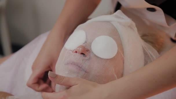 Profi kozmetikus készít arcot a maszk alkalmazásához.
