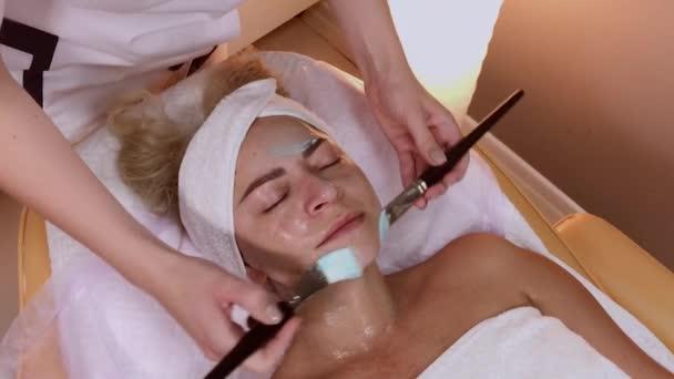 Profi kozmetikus a női arc kefével alkalmazva.