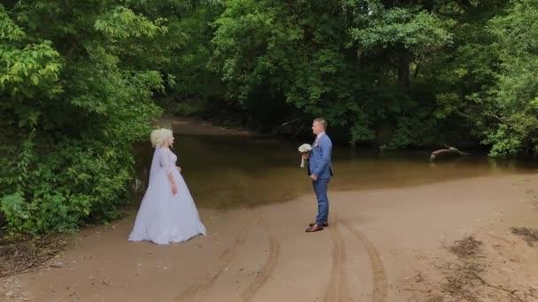 Krásný ženich a blonďatá nevěsta u potoka v lese.