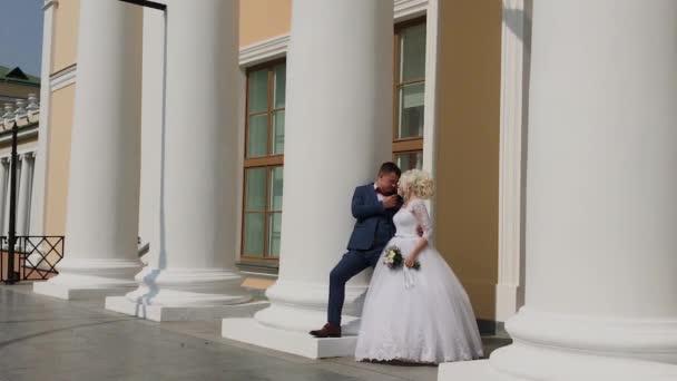 Šťastné novomanželé stojí ve sloupcích parku.