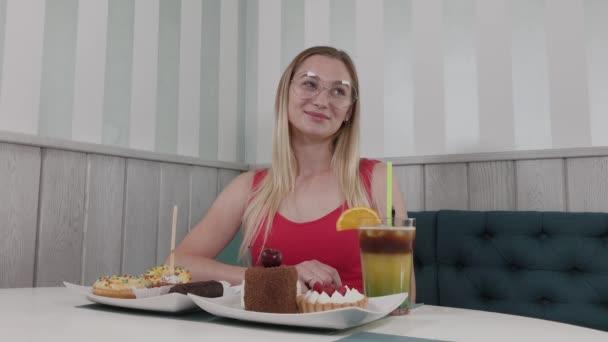 schöne junge Mädchen sitzt an einem Tisch in einem Café mit einem Teller Desserts.
