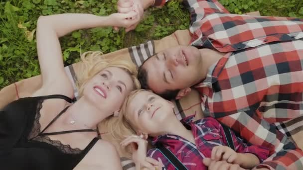 Šťastná rodina leží na trávě s hlavami na sobě.