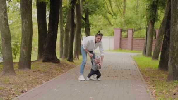Šťastná maminka chodí se svým synem v parku.