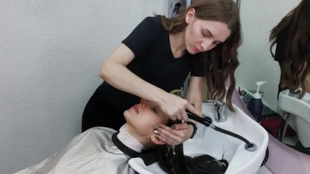 Gyönyörű fiatal lány mossa a haját a fodrásznál..