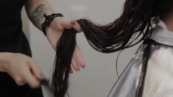 Dívka kadeřník česání mokré vlasy na klienta.