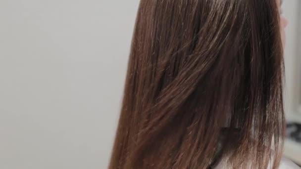 Dívka kadeřník suší vlasy na klienta s fénem na kadeřnictví.