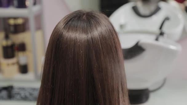Kadeřník aplikuje lak na vlasy na klienta.