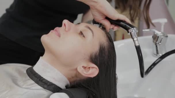 Krásná mladá dívka umýt své vlasy v kadeřnictví.