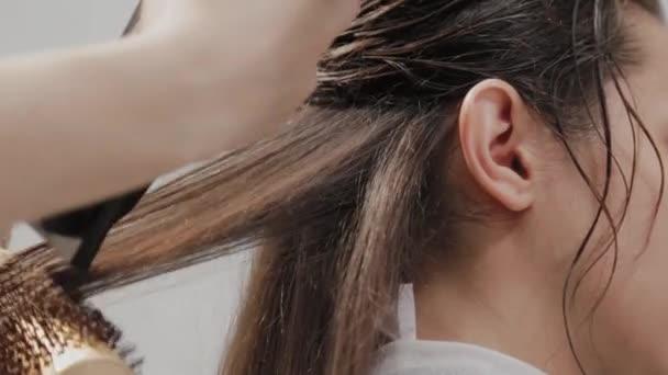 Lány fodrász szárítja haj ügyfél hajszárítóval a fodrásznál.