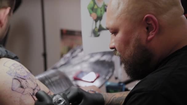 Professional tattoo artist makes a tattoo on a man s arm.