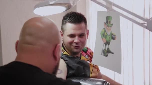 Profi tetováló művész csinál egy tetoválást egy férfi karjára.
