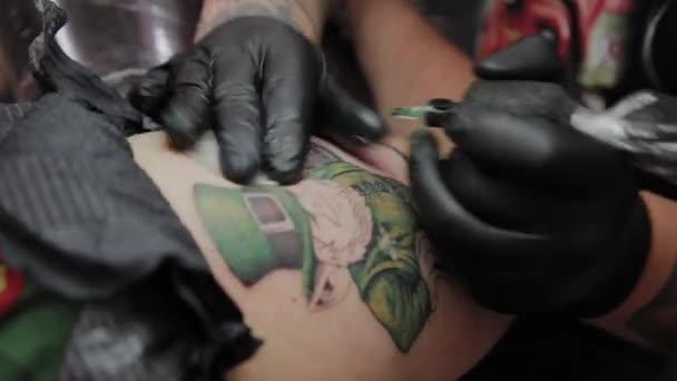 Profesionální tetování umělec dělá tetování na mužské ruce.