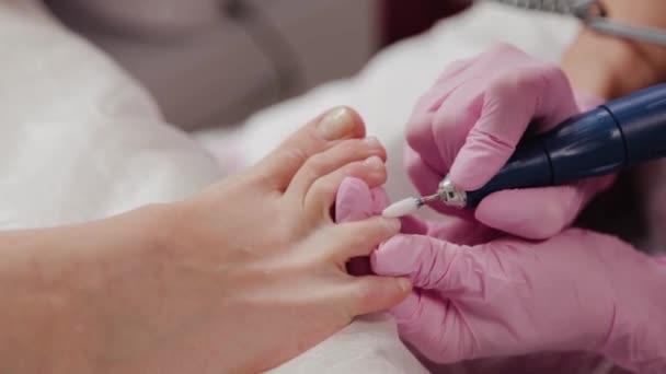 Pedikúra mistr řezání nehty na nohou ženy.
