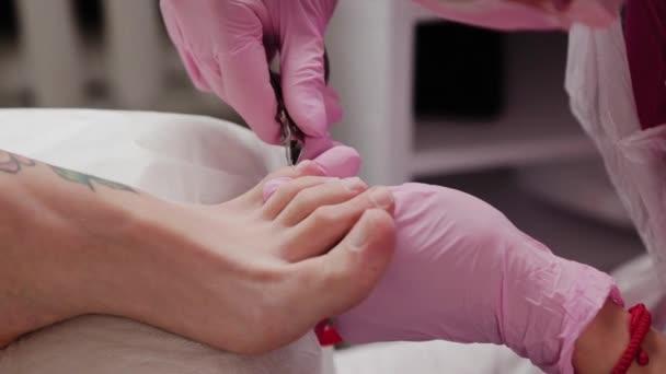 Pediküre-Meister schneidet Nagelhaut an Frauenbein.