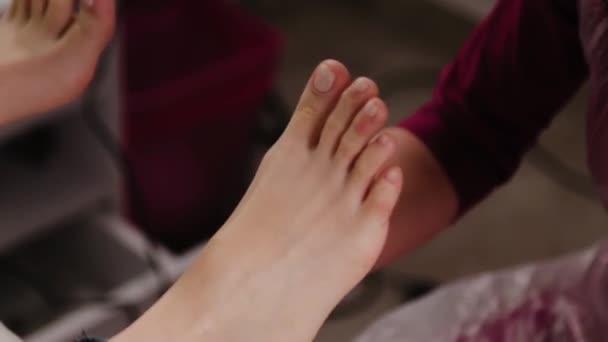 Pedikúra mistr dělá masáž nohou na ženu.