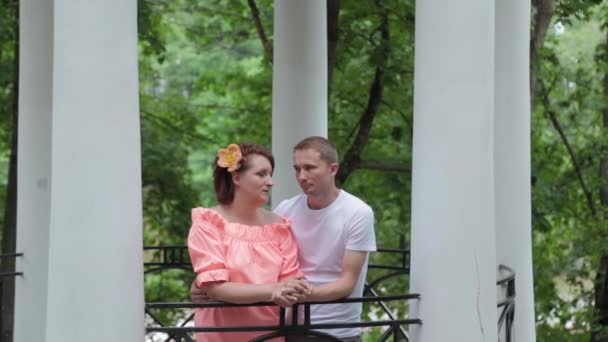 Young beautiful lovers in the park near the columns.