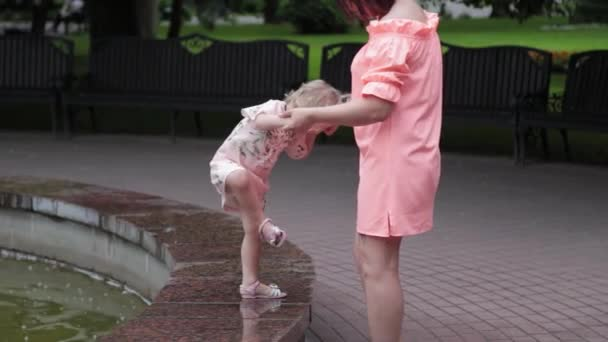 Happy mother with a child at the fountain.