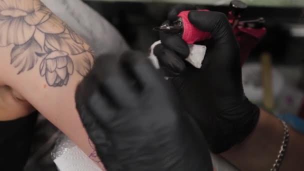 Tetováló művész csinál egy tetoválás egy fiatal lány kar.