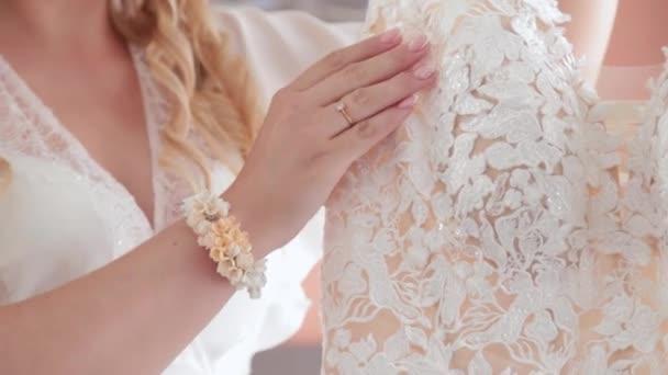 Női menyasszony simogatja a ruháját a kezével.