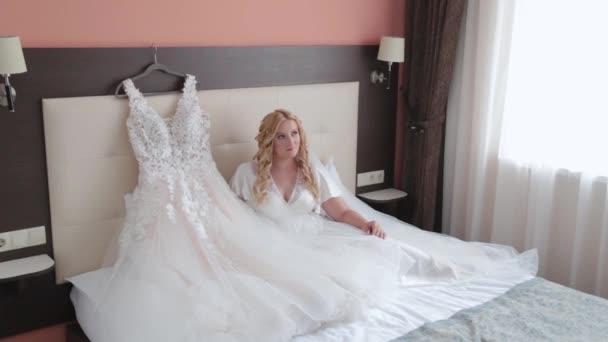 Žena nevěsta na posteli pózuje.