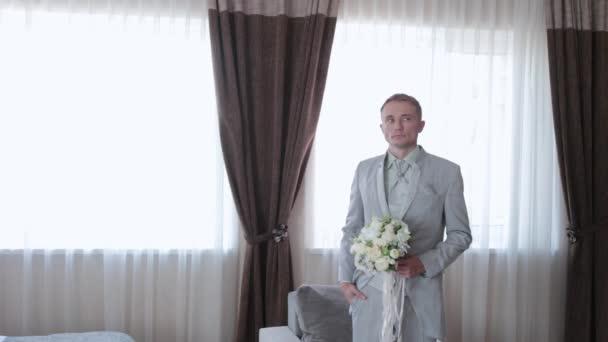 Jóképű férfi esküvői csokorral a kezében..