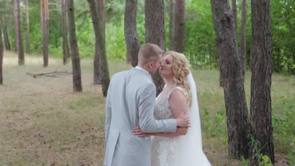 Nádherná nevěsta a ženich objímání a líbání v letním lese.