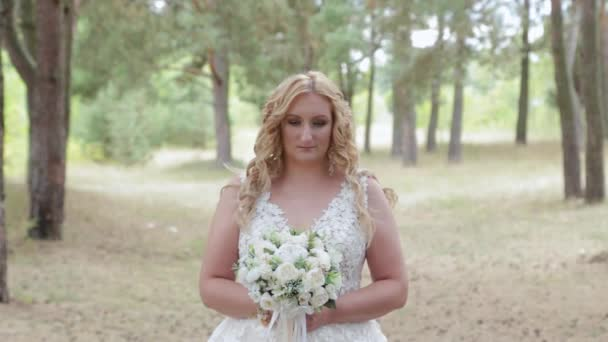 Bride with wedding bouquet in green summer forest.