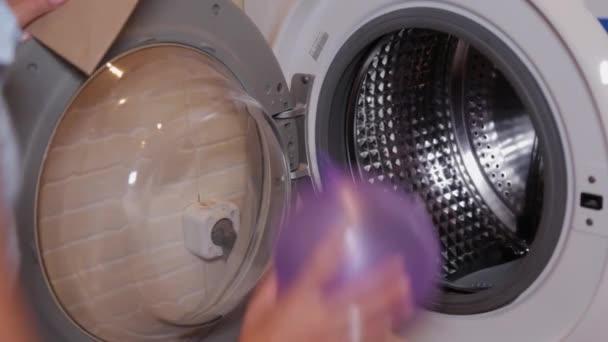 Egy nő lufikat rejteget a mosógépben..