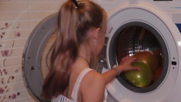 Glückliches Mädchen zieht Luftballons aus der Waschmaschine.
