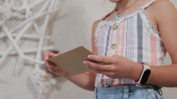 Krásná dívka s obálkou v ruce.