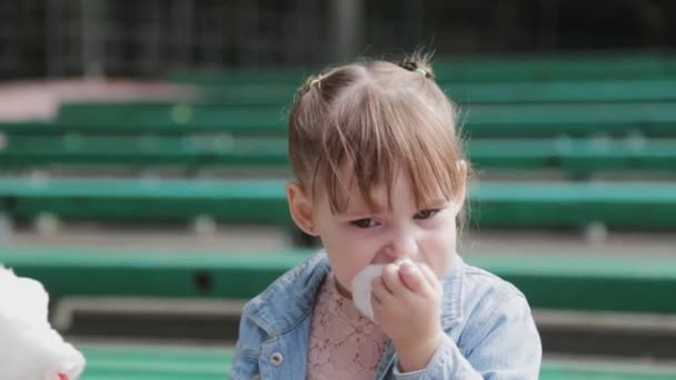 Beautiful and happy little girl eating cotton candy on the bench.