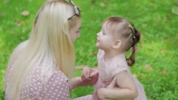 Mladá matka a malá dcera se baví v parku za slunečného počasí.