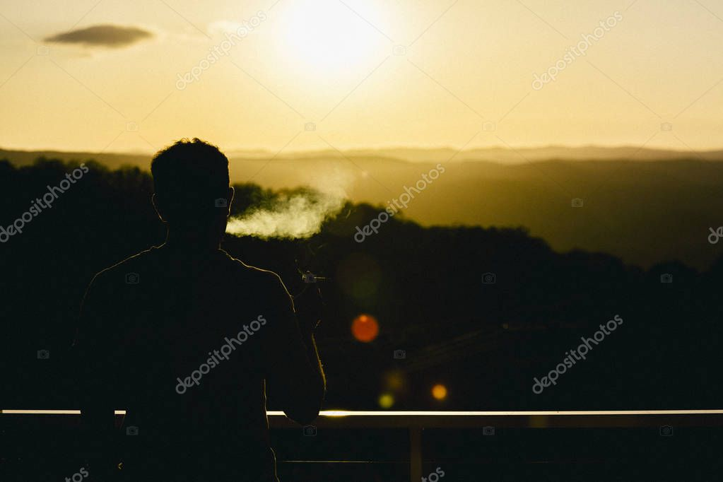 Silhouette of man smoking and watching the orange sun set