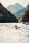 Mladý muž na kajaku na řece Dunajec, seděl v kajaku a pádlování po řece. Užívat si jízdu, obklopený kopci a krásný výhled na údolí a hory vrcholky. Tráví dovolenou na Putování s batohy horách a lesích