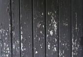 Fotografia Grungy peeling sfogliatura vernice nera su fondo di carta da parati di tavole di legno grigio closeup