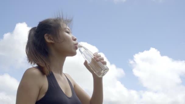 slowmotion shot woman drinking water after run