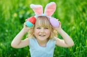 Cute funny girl with Easter eggs and bunny ears at garden. Easter concept. Laughing child at Easter egg hunt. Child in park with eggs, spring concept