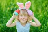 Roztomilá legrační dívka s velikonoční vajíčka a uši zajíček na zahradu. Velikonoční koncept. Smějící se dítě na velikonoční vajíčka. Děti v parku s vejci, jaro koncept