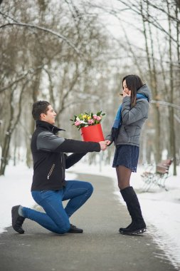 romantic offer to get married. man makes an offer to his girlfriend in winter park. Valentine day Proposal concept. Young man giving flower boquet for girlfriend in valentineday.