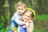 Bruder und Schwester sitzen auf dem Rasen. Spiele für Kinder, Freizeit. Zwei Kinder sitzen auf der grünen Wiese und Lächeln. Jungen und Mädchen zu küssen, an sonnigen Tag