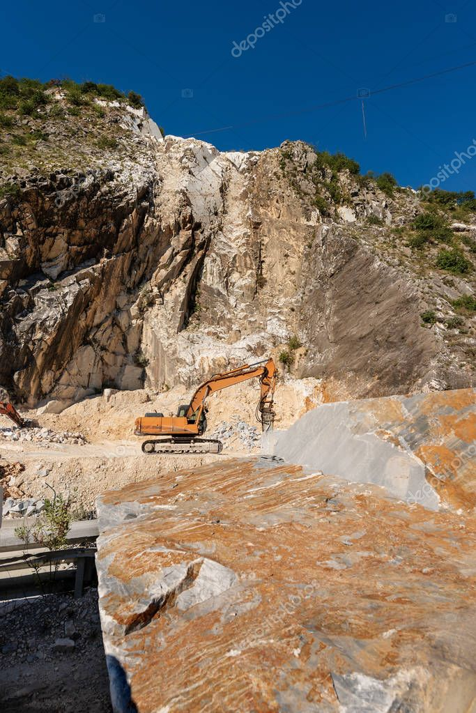 Orange tracked excavator with the jackhammer in a marble quarry (Carrara white marble) in the Apuan Alps (Alpi Apuane). Tuscany, (Toscana), Italy, Europe