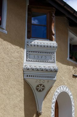 Small balcony with wooden windows in the ancient village of Zuoz, tourist resort in Engadin valley, Graubunden canton, Maloja region, Switzerland, Europe