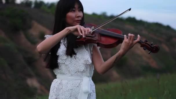 Ázsiai nő hegedűművész, fehér csipke ruha hegedül a háttérben a füvek és virágok a rét alkonyatkor. Vértes.