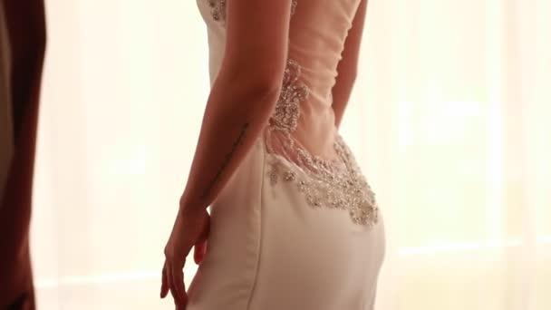 Nevěsta v krásné a stylové svatební šaty s perlami a vzor