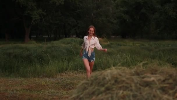 Young woman runs across meadow, jumps to haystack, rolls over and she has fun.