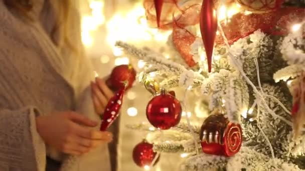 Young woman with plaid decorates branches of Christmas tree by toys. Closeup.