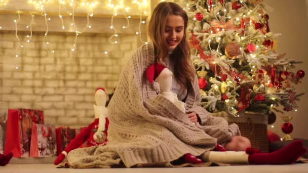 Young woman with plaid sits next to Christmas tree, smiles and plays with Santa Claus in her hands on background of sparkling light bulbs.